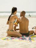 Woman applying suntan lotion on her boyfriend. Woman applying suntan lotion on her boyfriend on a sandy beach Stock Image