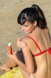 Woman applying suntan lotion in shoulder Stock Images