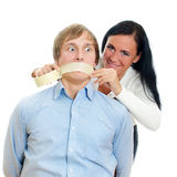 Woman applying tape on man's mouth. Stock Photos