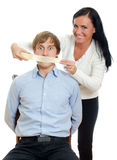 Woman applying tape on man's mouth. Royalty Free Stock Photography