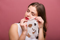 Woman applying a tissue mask Stock Photo