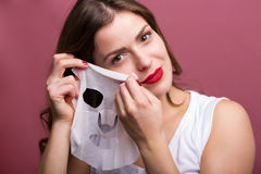 Woman applying a tissue mask Royalty Free Stock Image