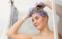 Woman applying toner shampoo on her hair stock image