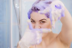 Woman applying toner shampoo on her hair royalty free stock image