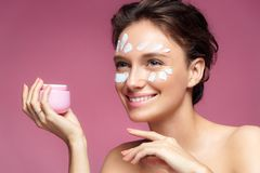 Woman applying wrinkle cream or anti-aging skin care cream Stock Photos