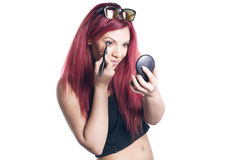 Woman applyng eyeliner looking in a pocket mirror. Red haired woman applyng eyeliner looking in a pocket mirror, smiling happy over white background Stock Photography