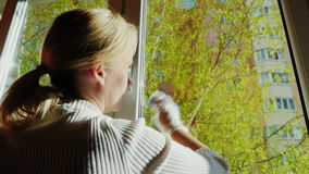 The woman approaches the window and begins to wipe it. Spring cleaning in the house. Back view stock footage