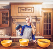 Woman in apron adds sugar into bowl, dough making Royalty Free Stock Photo