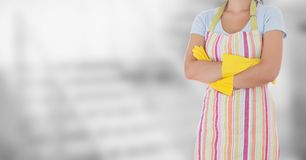 Woman in apron arms folded against blurry grey background Royalty Free Stock Images