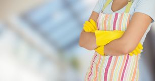 Woman in apron with arms folded against blurry window Stock Image