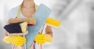 Woman in apron with brushes against blurry grey room Royalty Free Stock Image