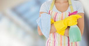 Woman in apron with cleaner against blurry window Royalty Free Stock Images