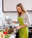 Woman in apron cooking   soup Stock Photo