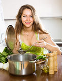 Woman in apron cooking  soup Stock Photography