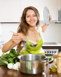 Woman in apron cooking  soup in kitchen Stock Photography