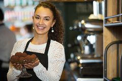 Woman in the apron with delicious chocolate truffles. Hospitable girl with delicious chocolate truffles in coffe-house serves truffels waiting for customers stock photo
