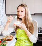 Woman in apron eating curd cheese Royalty Free Stock Photography