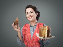 Woman in apron eating panettone Royalty Free Stock Photos