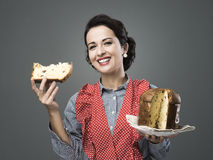 Woman in apron eating panettone Royalty Free Stock Images