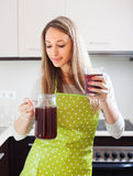 Woman in apron with fresh quass in glass Royalty Free Stock Photos