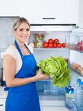 Woman in apron holding bottle Stock Photos