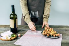 Woman in apron holding glass of wine. In a hand Royalty Free Stock Image