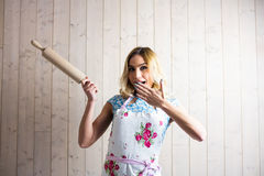 Woman in apron holding a rolling pin against texture background Stock Image