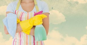Woman in apron holding spray bottle against sky background Royalty Free Stock Photos
