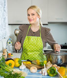 Woman in apron at home kitchen Stock Photo