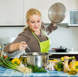 Woman in apron at kitchen Stock Photography