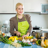 Woman in apron at kitchen Stock Photos