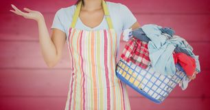 Woman in apron with laundry against blurry pink wood panel. Digital composite of Woman in apron with laundry against blurry pink wood panel Stock Images