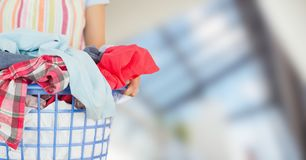 Woman in apron with laundry against blurry window Stock Image