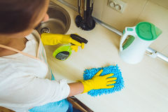 The woman in an apron makes cleaning Royalty Free Stock Photography