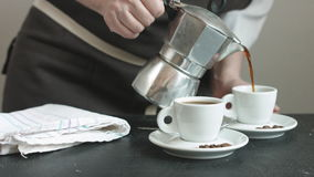 Woman in the apron pouring fresh hot coffee. Side view of woman in the apron pouring fresh hot coffee in two small cups stock footage