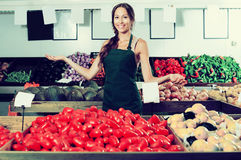 Woman in apron selling organic tomatoes in shop Royalty Free Stock Images