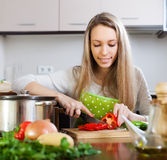Woman in apron slicing  pepper at table Stock Images