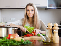 Woman in apron slicing  pepper at table Royalty Free Stock Photo