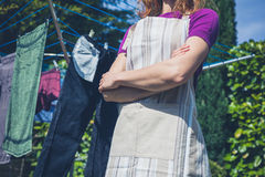 Woman in apron standing by clothes line Royalty Free Stock Photo