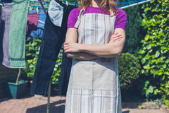 Woman in apron standing by clothes line Stock Photography