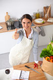 Woman in apron standing on the desk with grocery Royalty Free Stock Photos