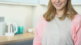 Woman in apron standing in kitchen and smiling to camera, housewife portrait. Stock footage stock video