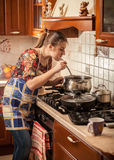 Woman in apron stirring soup with kitchen spoon Royalty Free Stock Photo