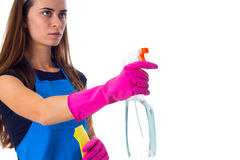 Woman in apron using detergent and duster. Young beautiful woman with long hair in blue T-shirt and apron with pink gloves using yellow duster and detergent on Stock Photos
