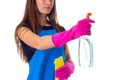 Woman in apron using detergent and duster. Young pretty woman with long hair in blue T-shirt and apron with pink gloves using yellow duster and detergent on Stock Photos