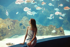 Woman in the aquarium watching the fish Royalty Free Stock Photos