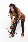 Woman with arbalest. Full-length portrait of beautiful woman fur hunter reloading crossbow on gray stock photo