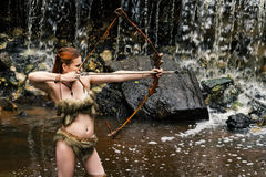 Woman archer shoots bow on background waterfall Stock Image