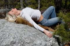 Woman arching her back. Woman arches her back while lying on a boulder Royalty Free Stock Photography