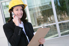 Woman Architect. A pretty woman architect holding blueprints and talking on the phone Royalty Free Stock Photo